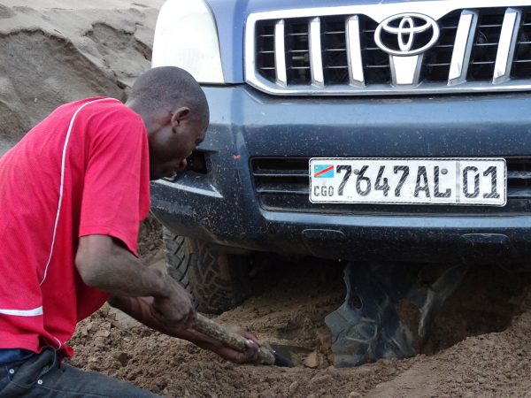 19 Our driver, Reagan Matu, digging the engine protection plate that is broken. This happen after having already broken two tires and the assisted direction of the steering wheel